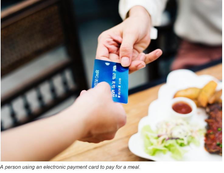 A Person Using An Electronic Payment Card To Pay For A Meal