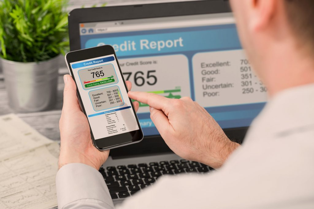 Man holding a smartphone calculating his average credit score.