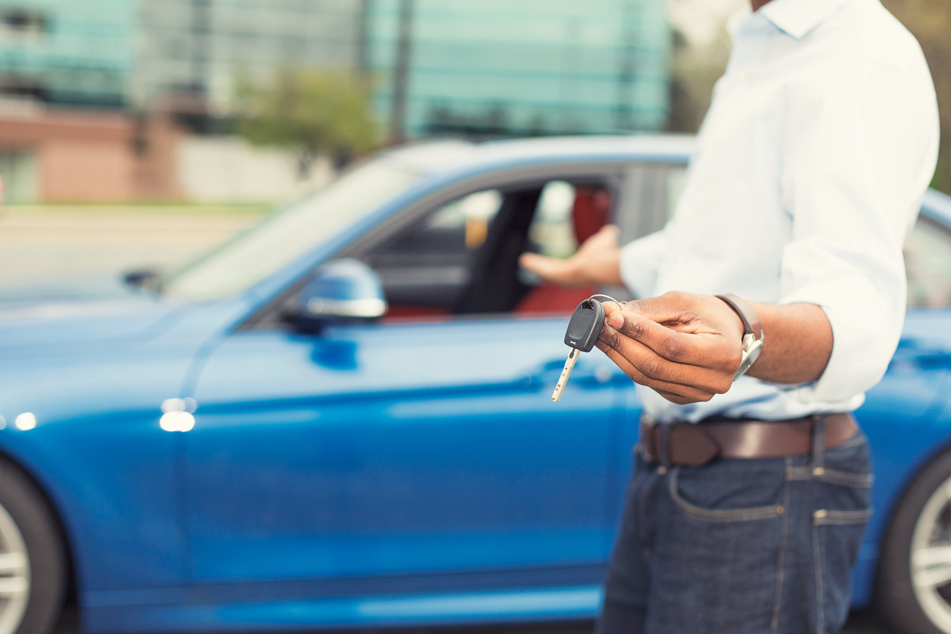 Man holding car keys in front of his newly leased car.